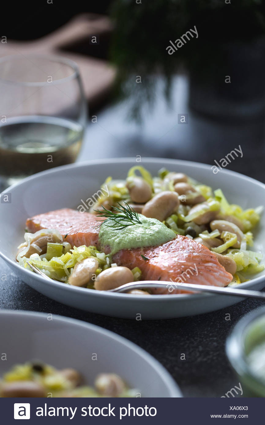 Une assiette pleine de haricots beurre blanc garni de tranches de saumon cuit au four est photographié à partir de la vue de face. Photo Stock