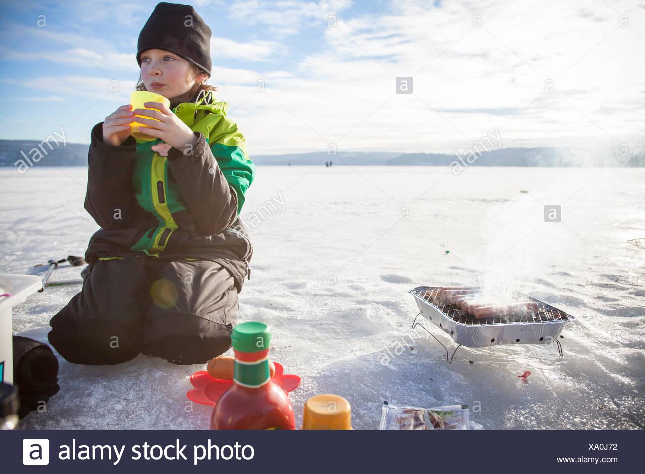 Boy (8-9) boire du thé en plein air Photo Stock