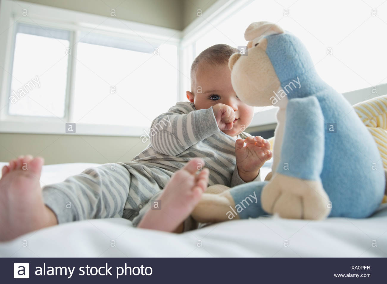 Bébé avec animal en peluche sur le lit Photo Stock