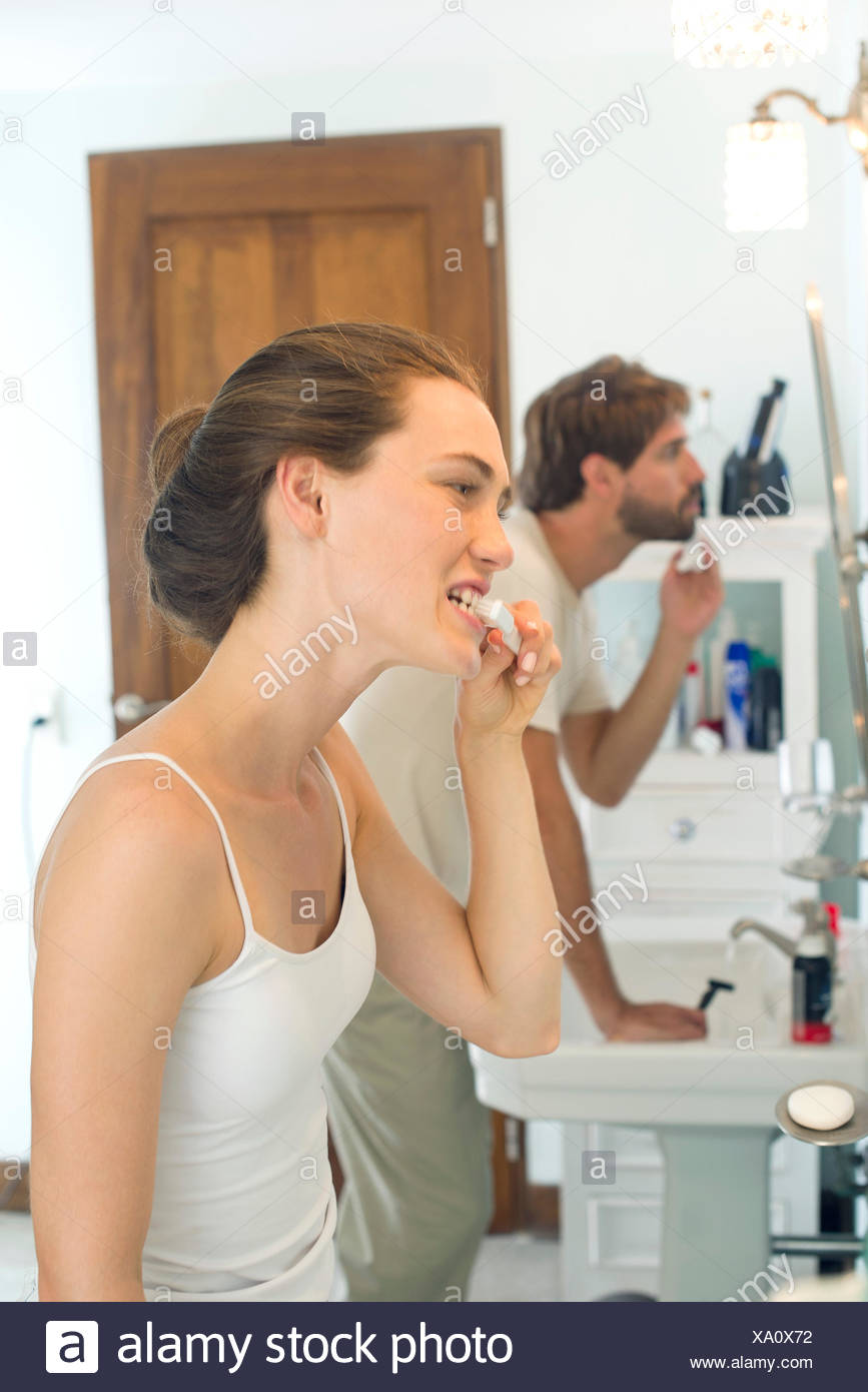 Femme se brosser les dents, mari de Photo Stock
