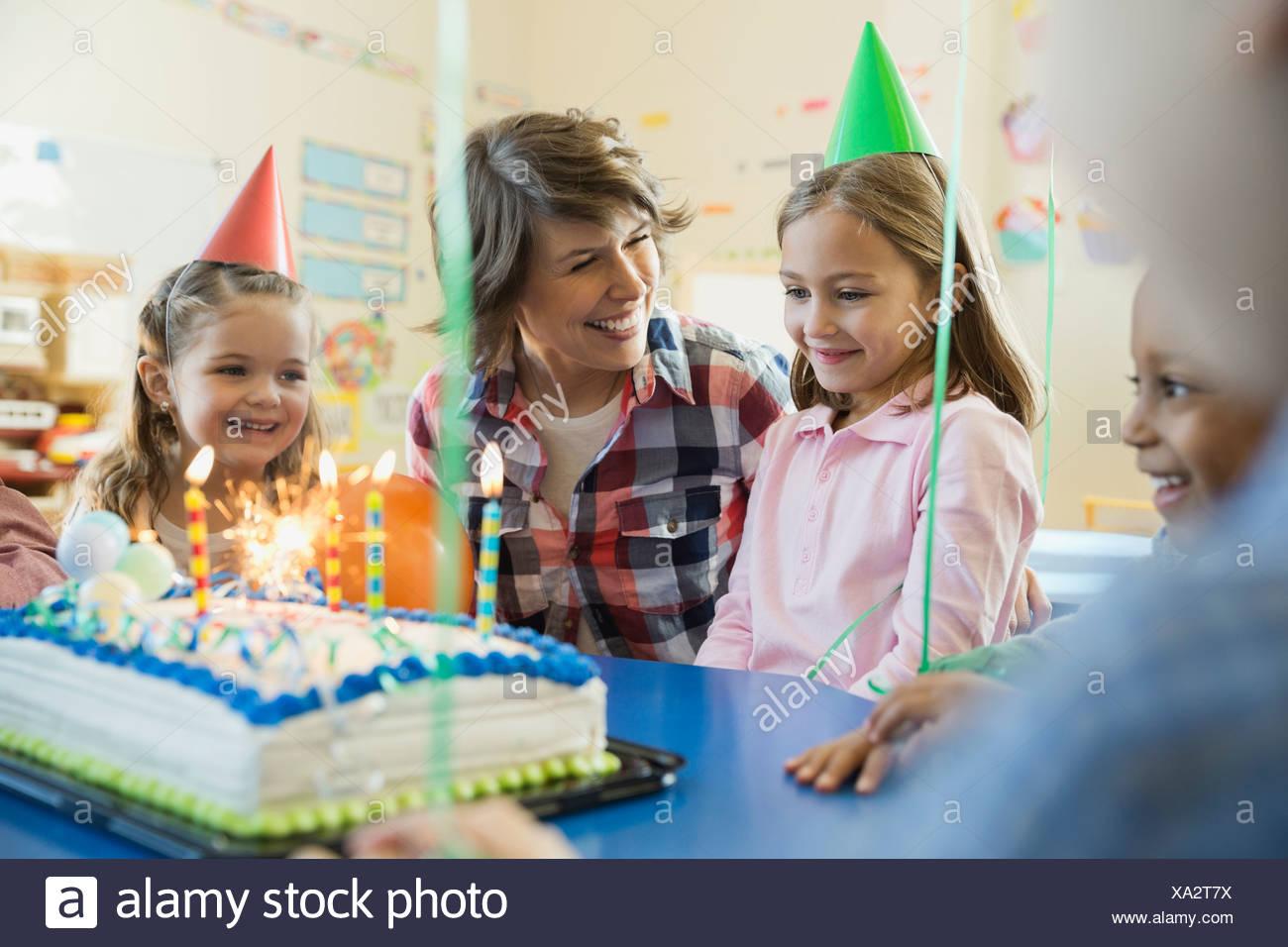 Avec l'enseignant les enfants célébrer anniversaire à l'école élémentaire Photo Stock