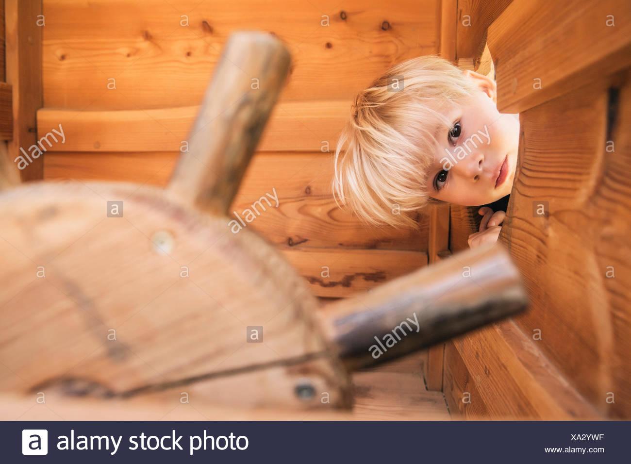 Petit garçon à travers l'orifice du bateau en bois sur l'aire de jeux Photo Stock