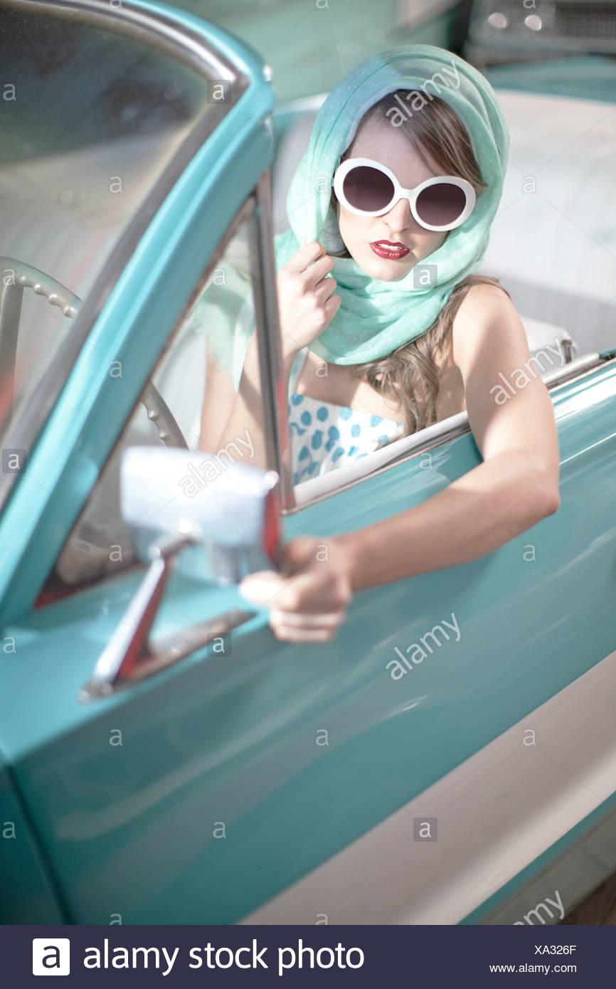 Femme au foulard et lunettes blanches en décapotable vintage Photo Stock