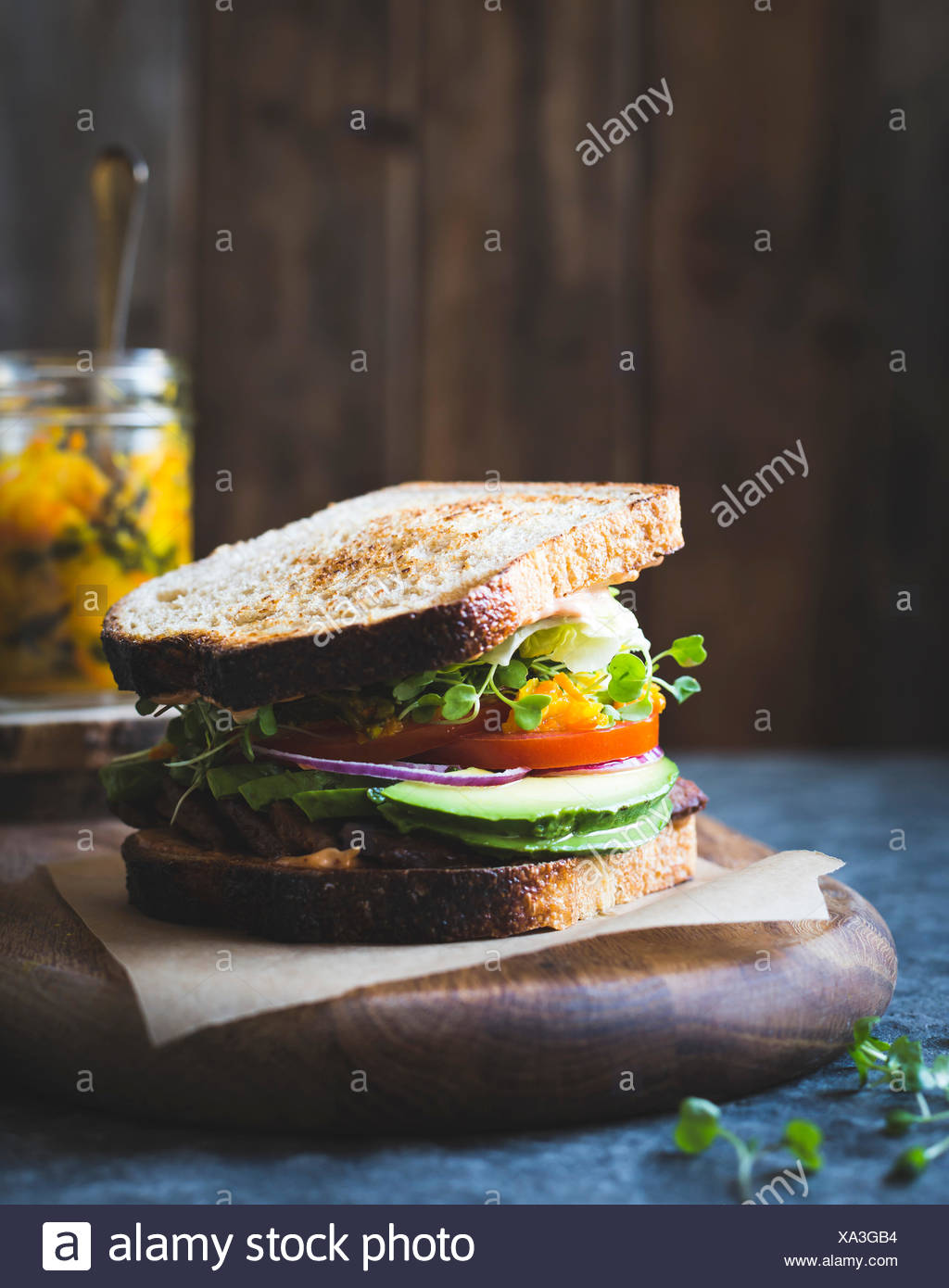 Cet bacon, laitue, tomate sandwich avec du kimchi, avocat et mayonnaise chipotle Photo Stock