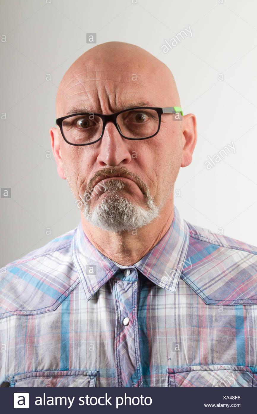 Portrait Portrait d'homme en colère contre lunettes en arrière-plan gris Photo Stock