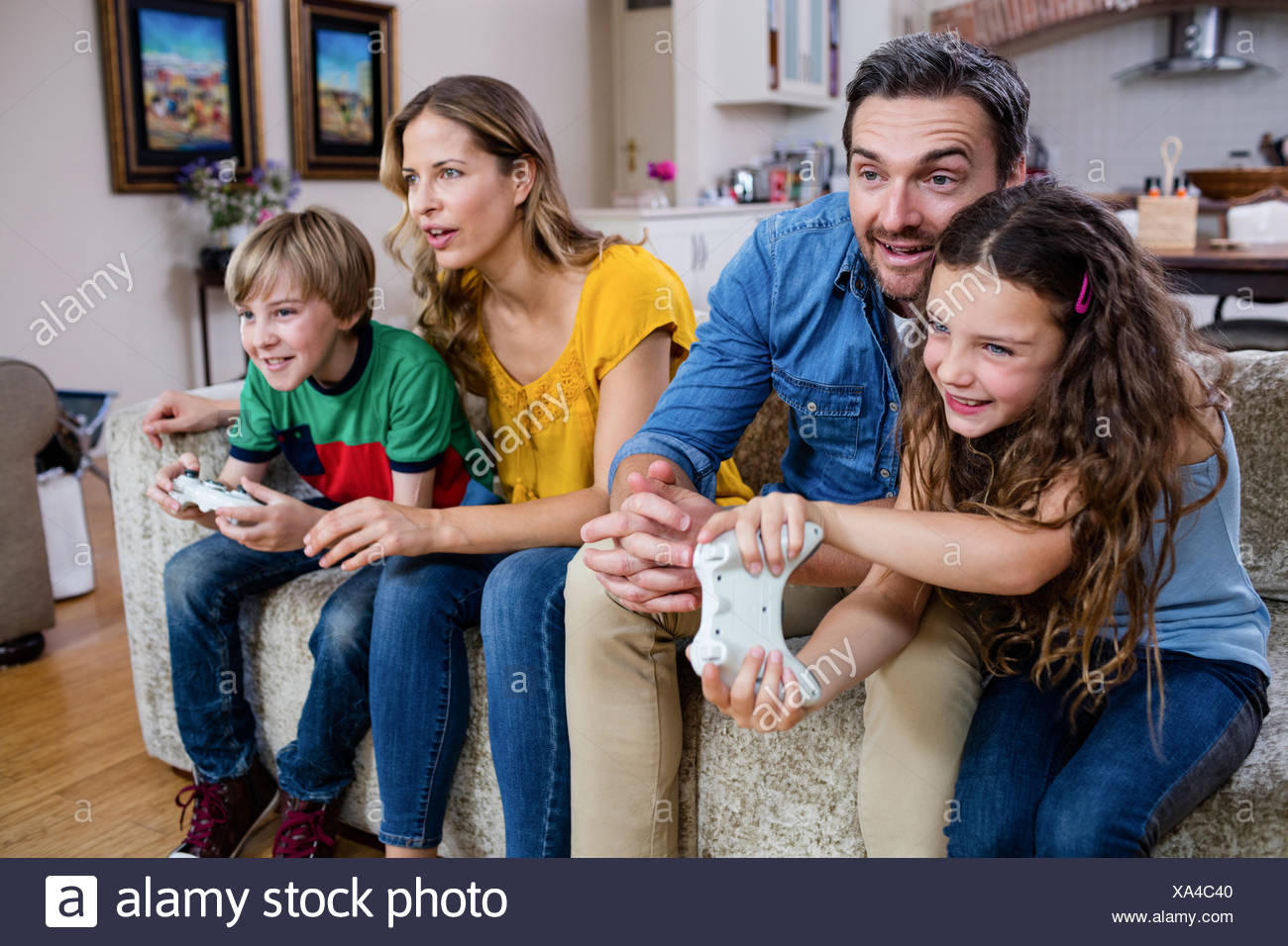Family sitting on sofa and playing video game Photo Stock