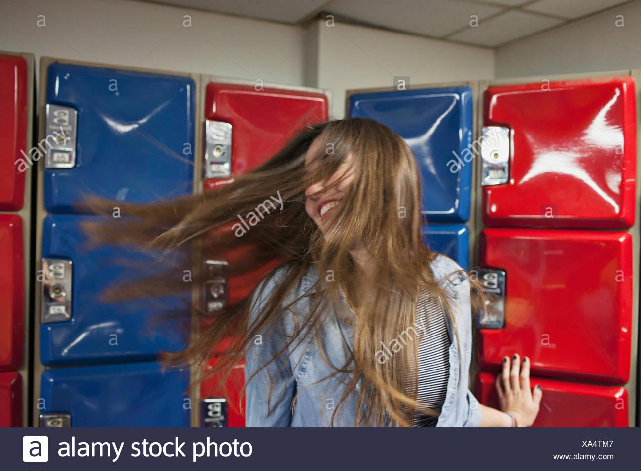 Une jeune femme par certains casiers rouge et bleu. Photo Stock