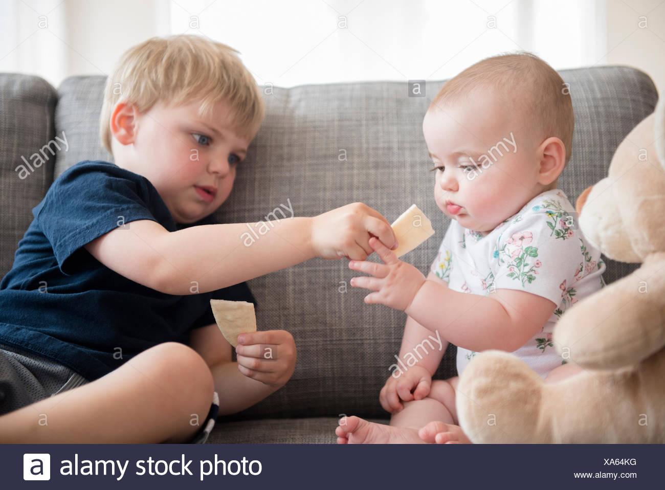 Frère (2-3) partage les craquelins avec petite sœur (12-17 mois) Photo Stock