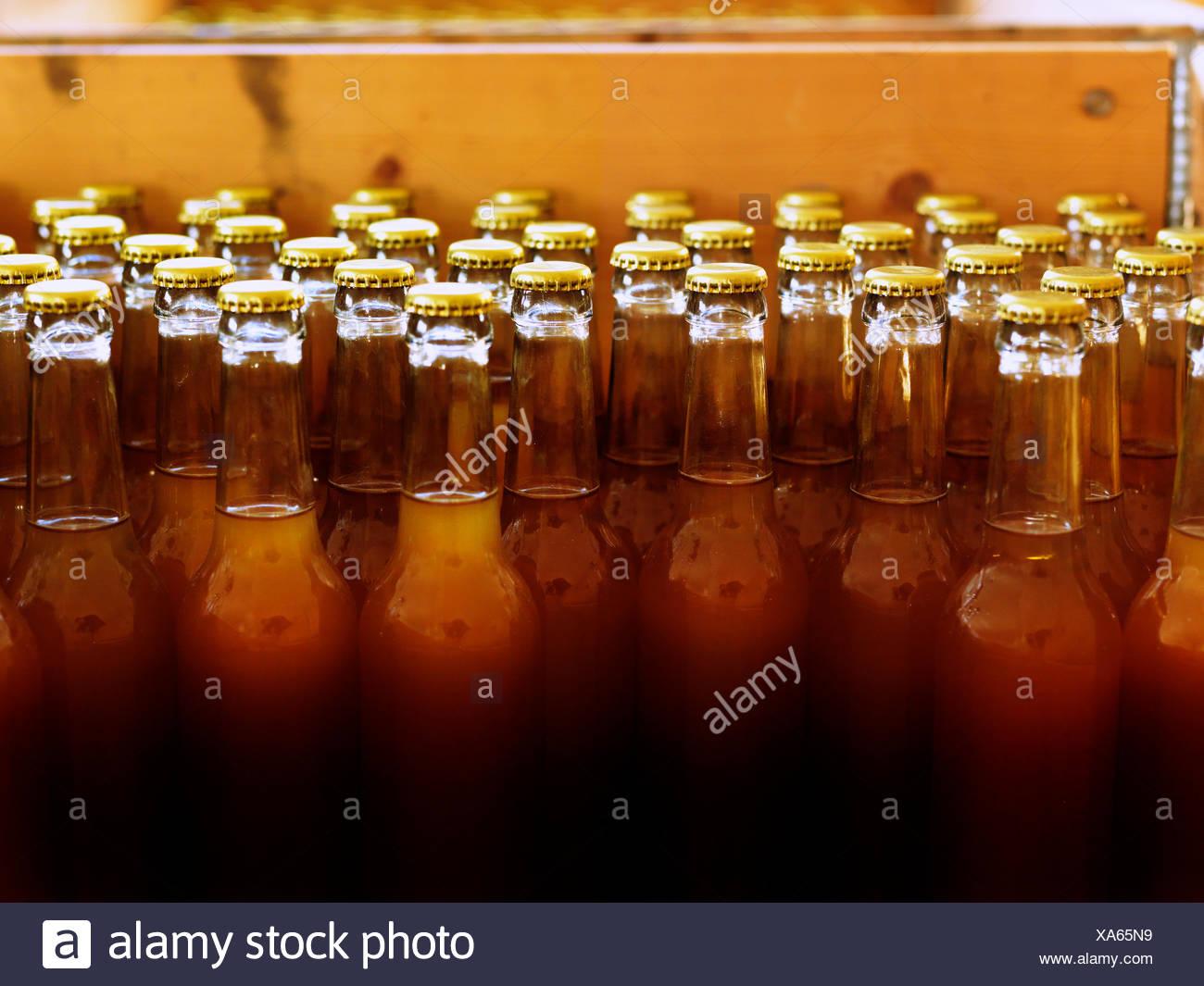 La Suède, avec des bouteilles non étiquetées et tops fermé rempli de lumière liquide brun foncé Photo Stock
