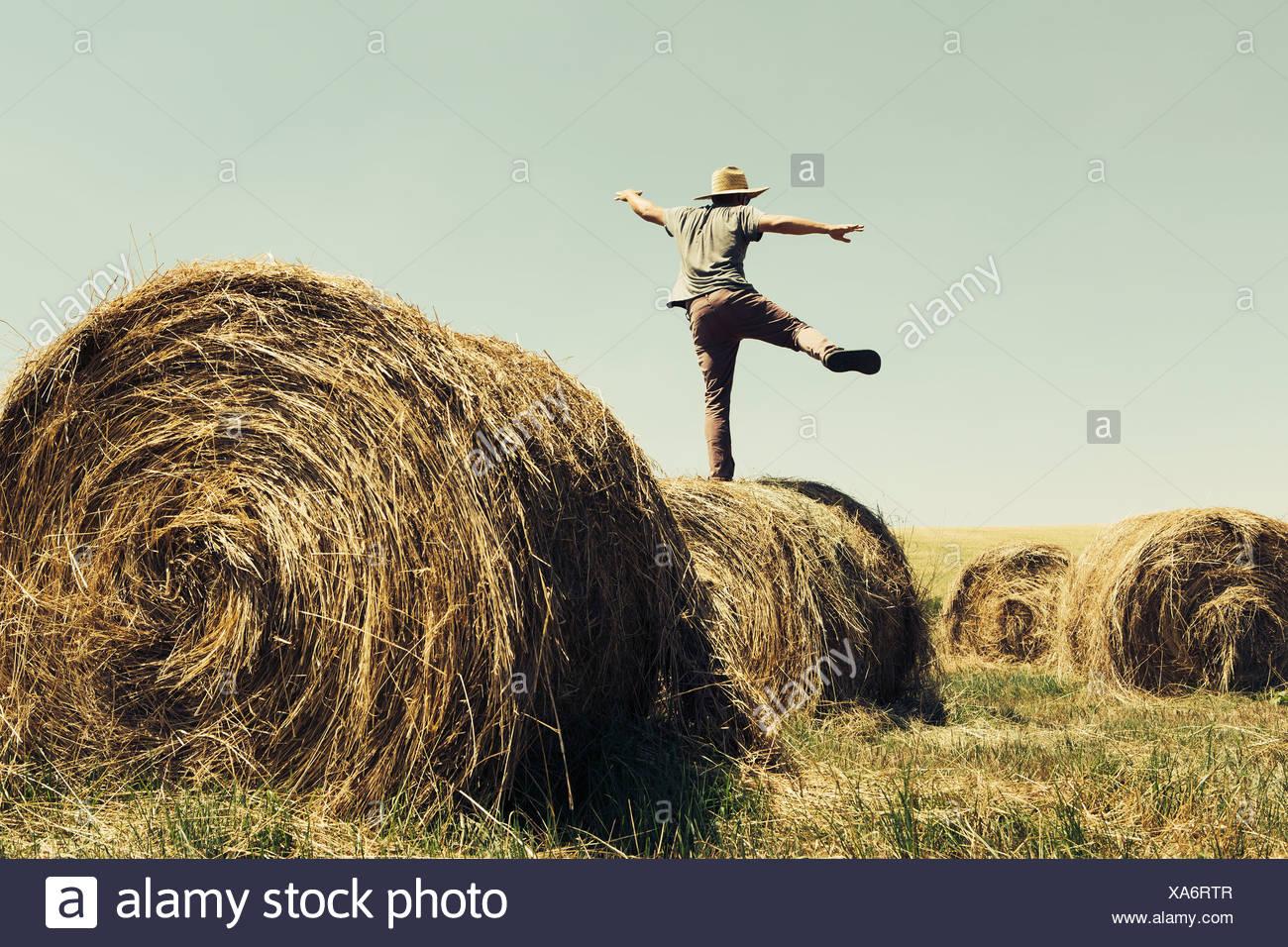 Vue arrière d'un homme en équilibre sur une jambe sur le dessus d'une balle de foin. Banque D'Images