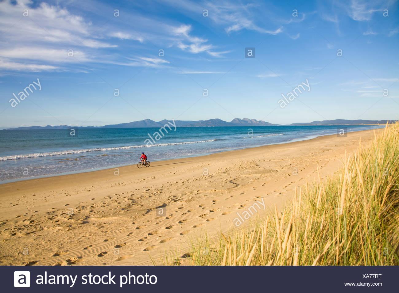 Une femme bénéficiant d'une promenade en vélo sur 9 Mile Beach sur la côte est de la Tasmanie, en Australie. Photo Stock