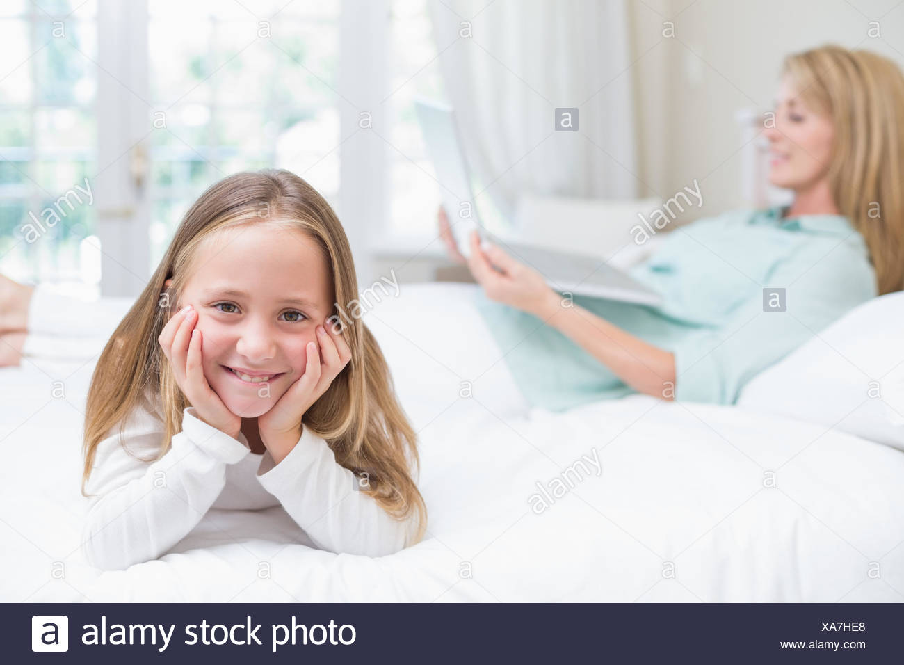 Little girl looking at camera while mother using laptop Photo Stock