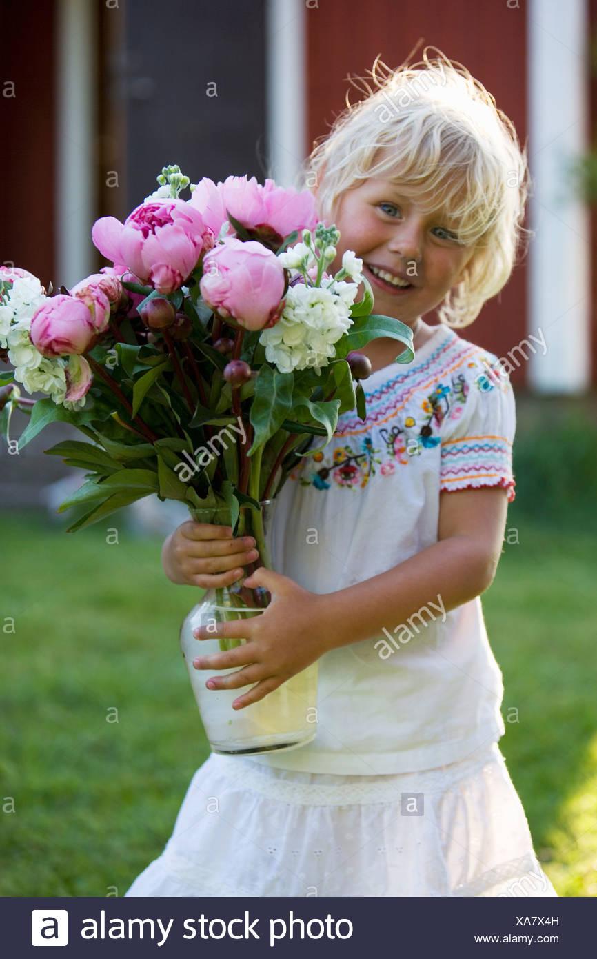 Little girl holding a bouquet de fleurs, Fejan, archipel de Stockholm, Suède. Banque D'Images
