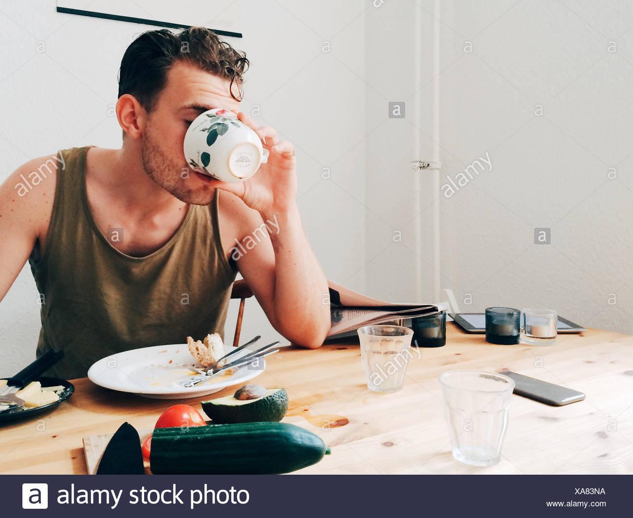L'homme de boire du café par table en désordre Photo Stock