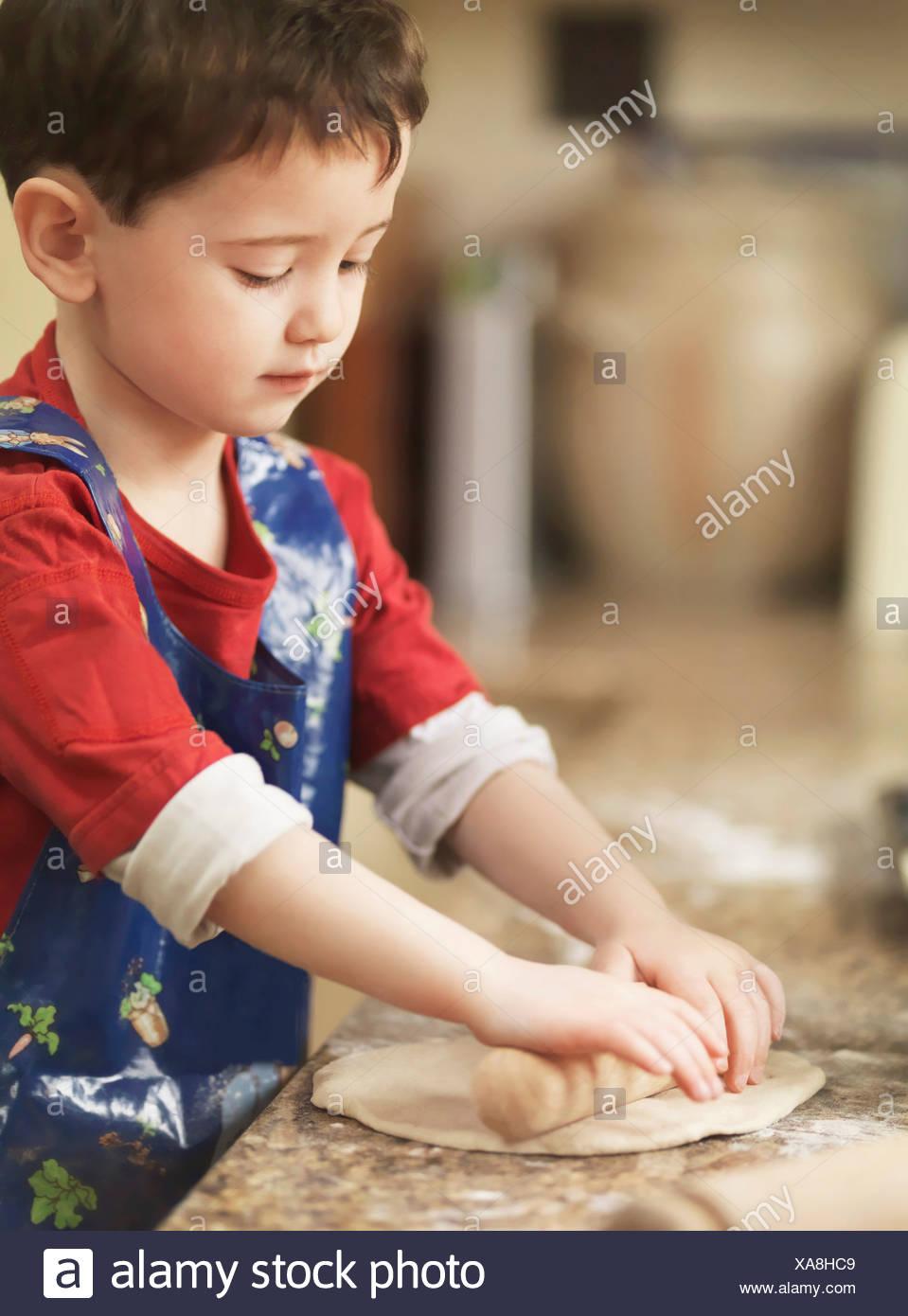 Pétrir la pâte avec l'enfant Rolling pin Photo Stock