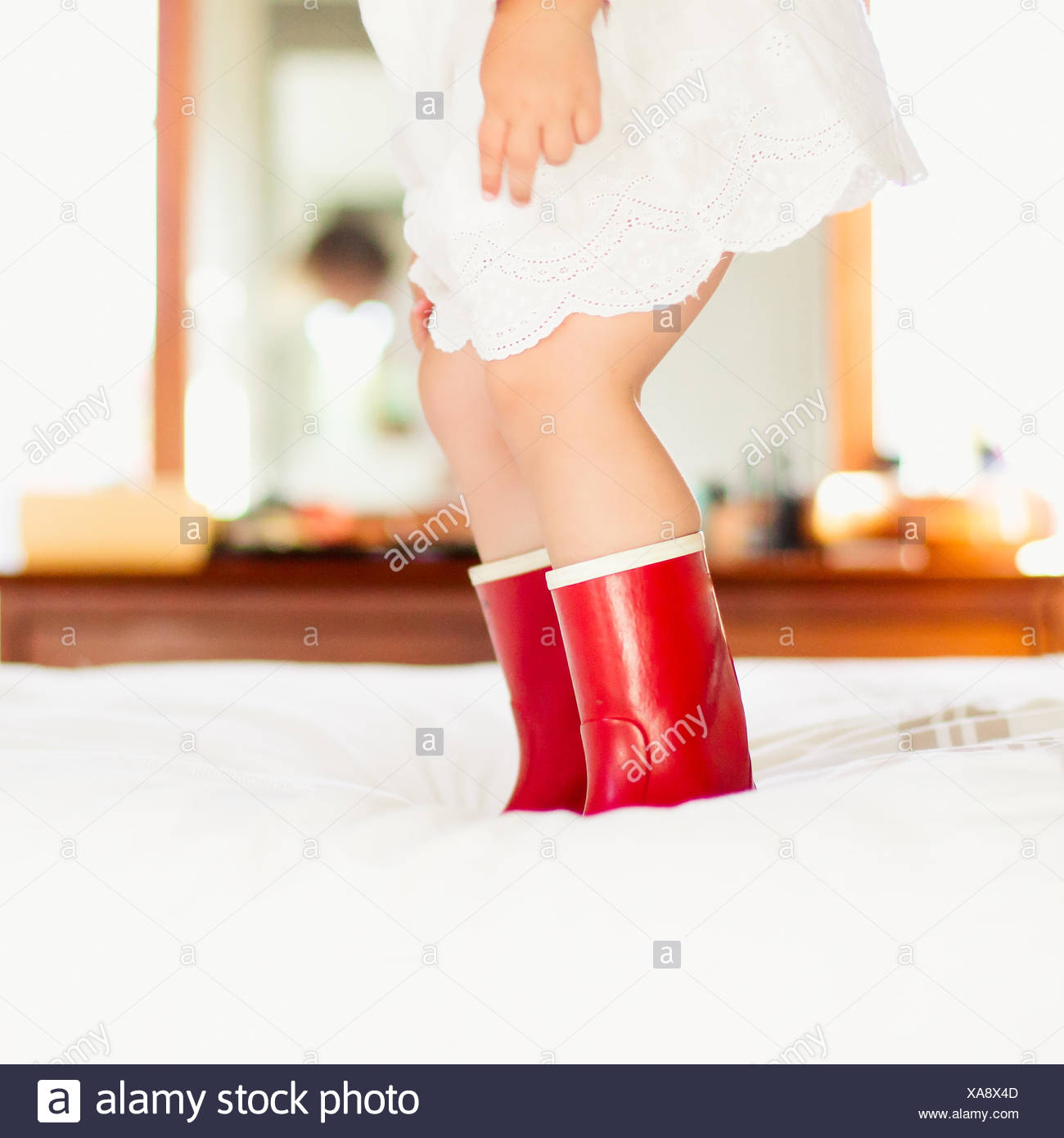 Close-up of a Girl in red boots sauter sur un lit Photo Stock