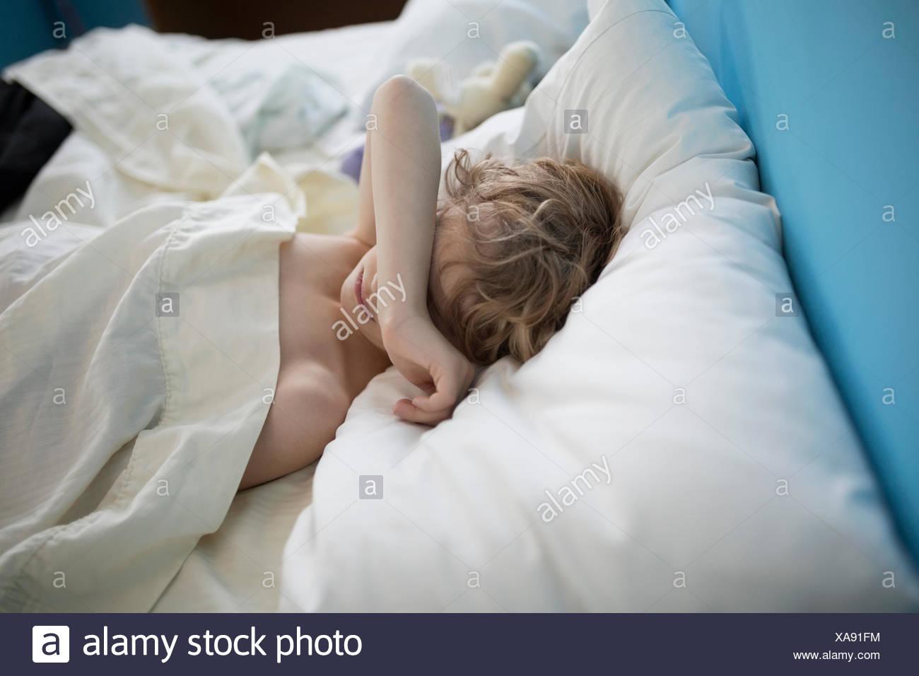 Fatigué garçon endormi avec le bras au-dessus des yeux Photo Stock