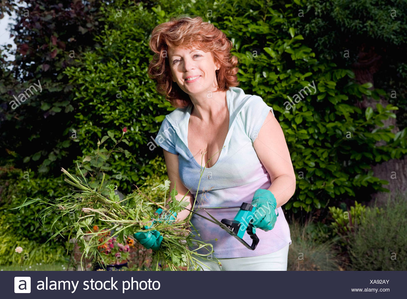 Mature Woman holding plants in garden Photo Stock