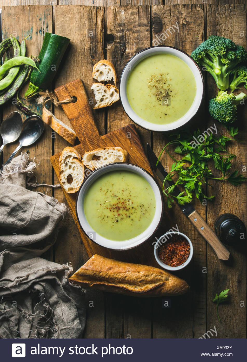Deux bols de pois fait maison, le brocoli et la courgette soupe crème servi avec baguette fraîche et légumes sur planche de bois plus rusti Photo Stock