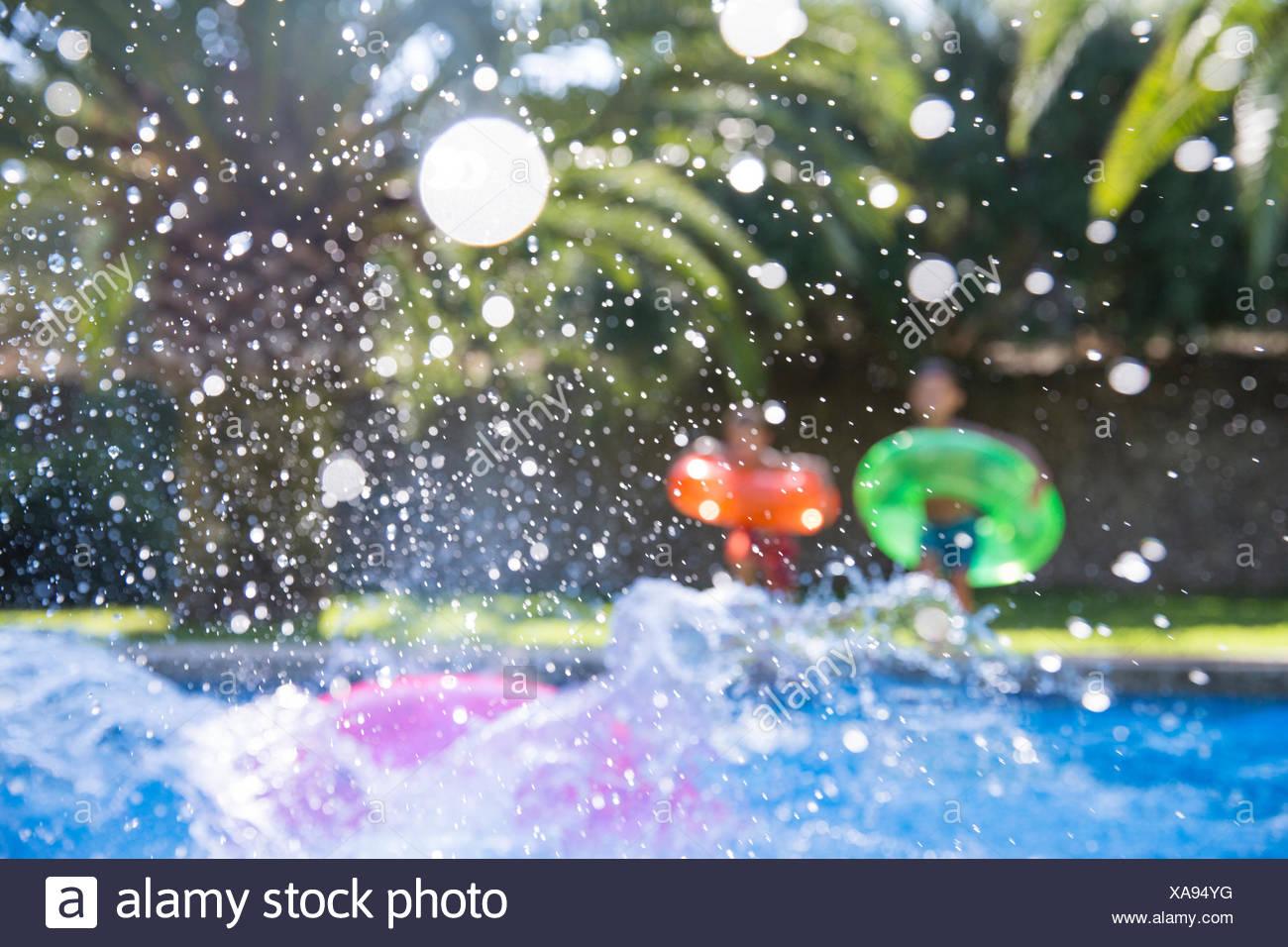 Trois enfants making a splash dans jardin piscine Photo Stock