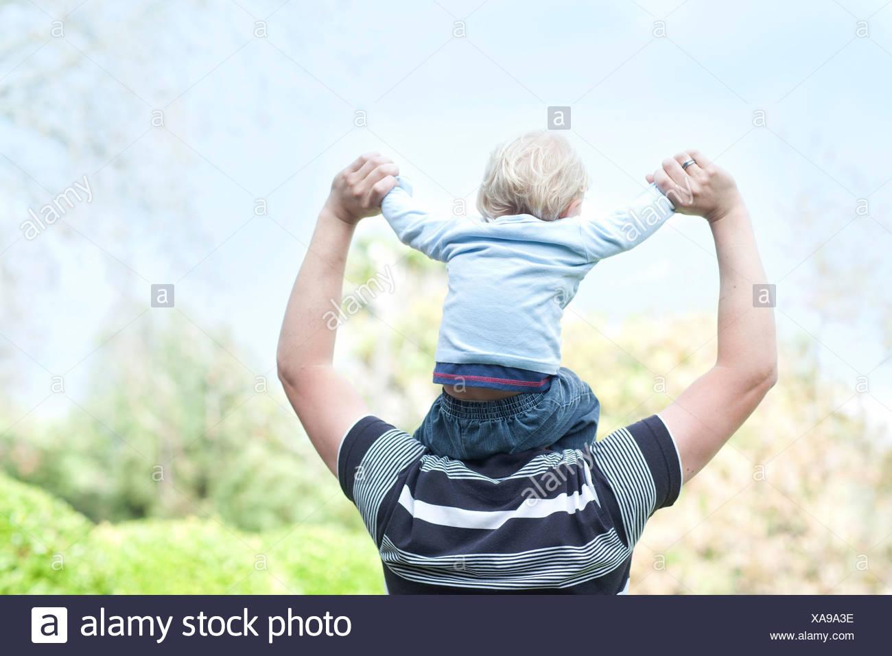 Le père avec son fils sur les épaules de bébé Photo Stock