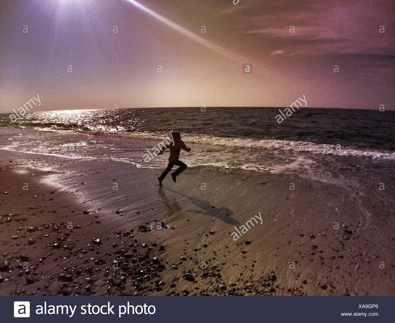 Boy Running On Beach contre ciel lors de journée ensoleillée Photo Stock