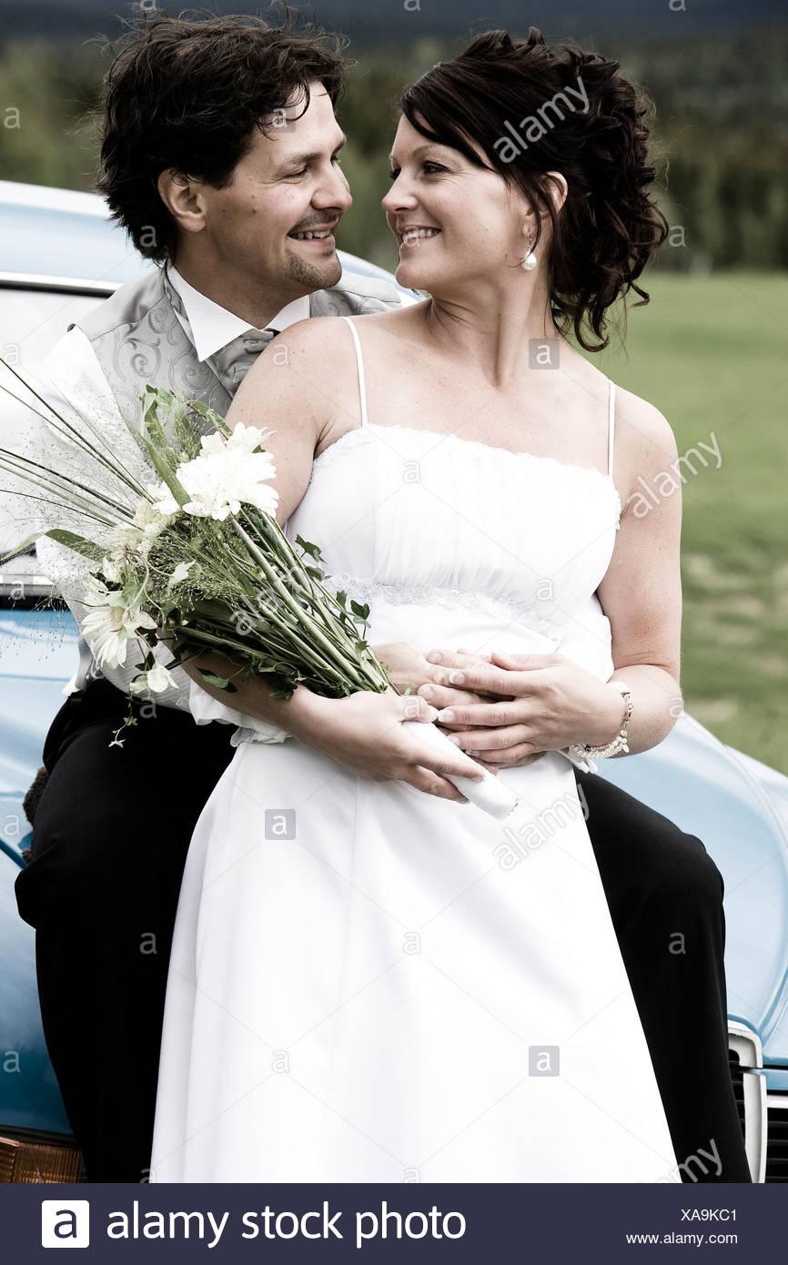 Heureux de Faire place au marié mariée de derrière comme ils regardent les uns les autres Banque D'Images
