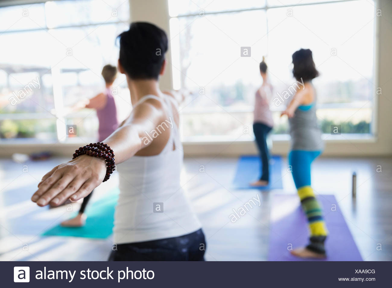 Les femmes pratiquant guerrier 2 poser dans la classe de yoga Photo Stock