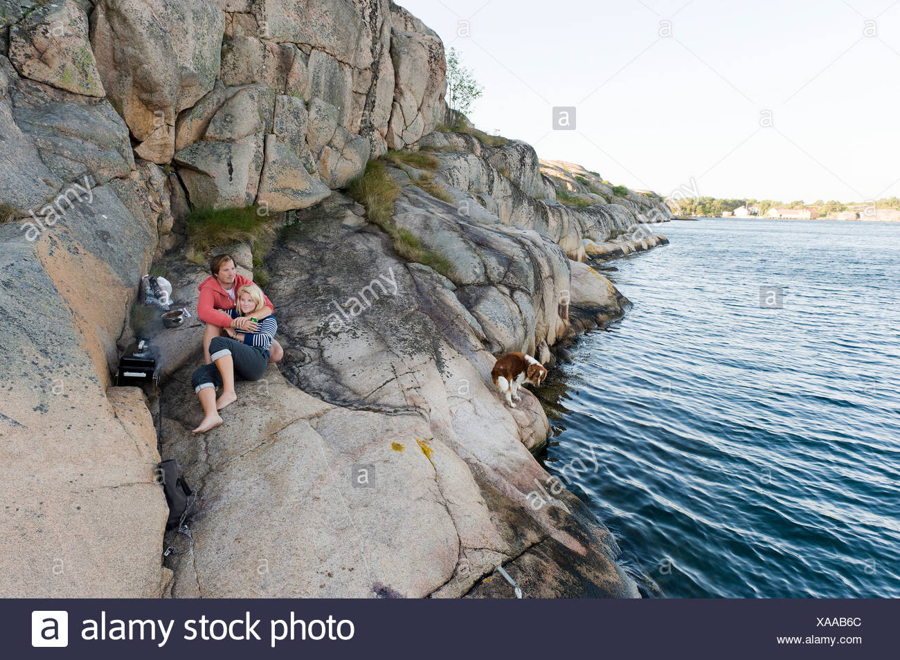 Détendue et romantique teenage boy and girl sur le rocher par la mer pacifique Photo Stock