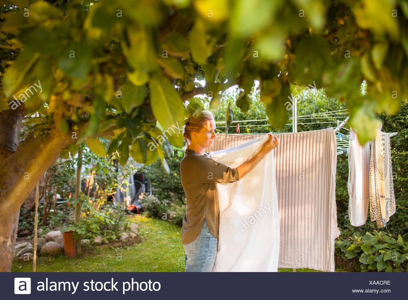 Femme étendre le linge sur la corde à linge dans la cour Photo Stock