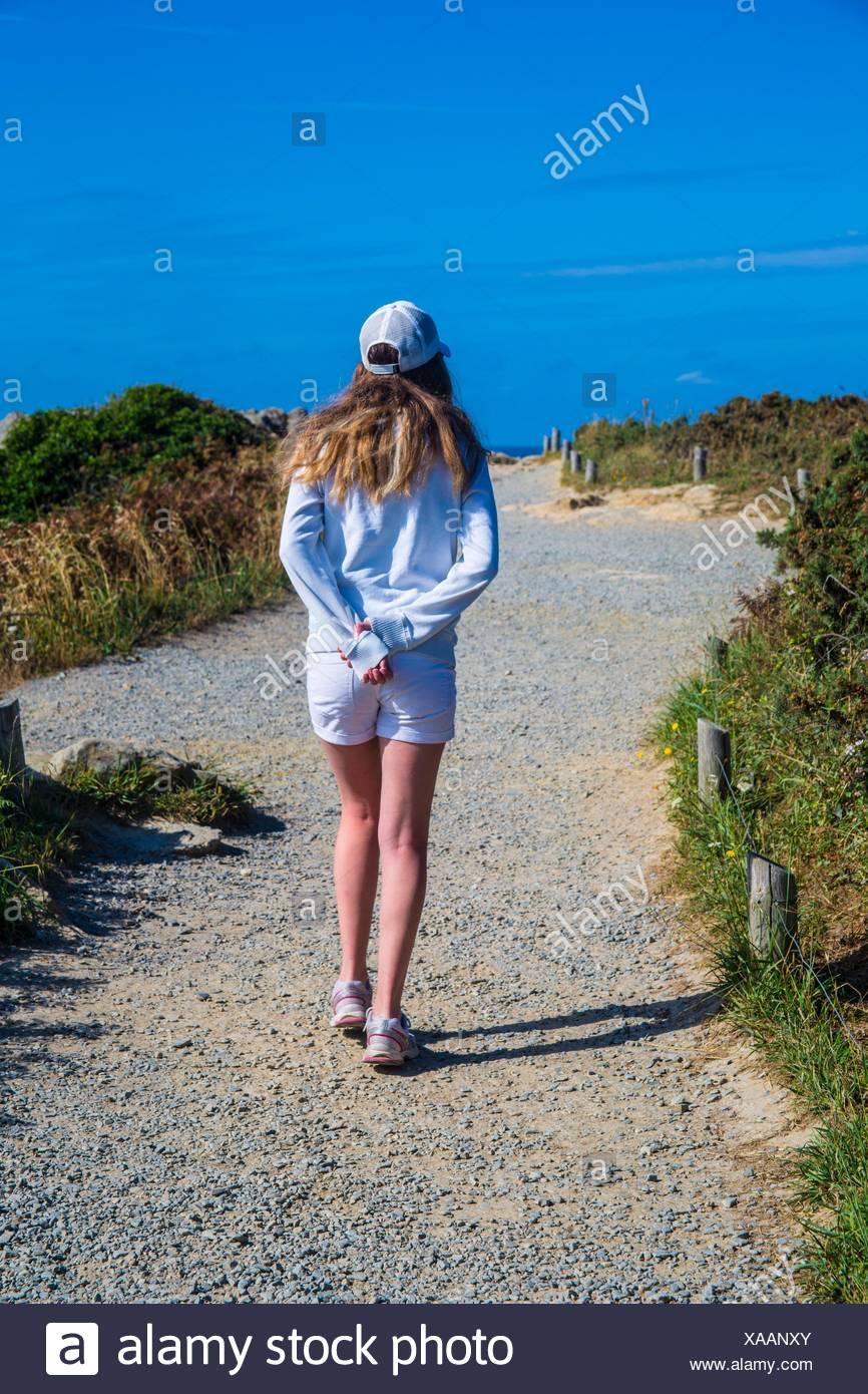 Pré-ado/ teen avec de longs cheveux blonds et une casquette de baseball et de passage les mains derrière le dos, marchant sur le bord d'un chemin de gravier avec le point de vue de l Photo Stock