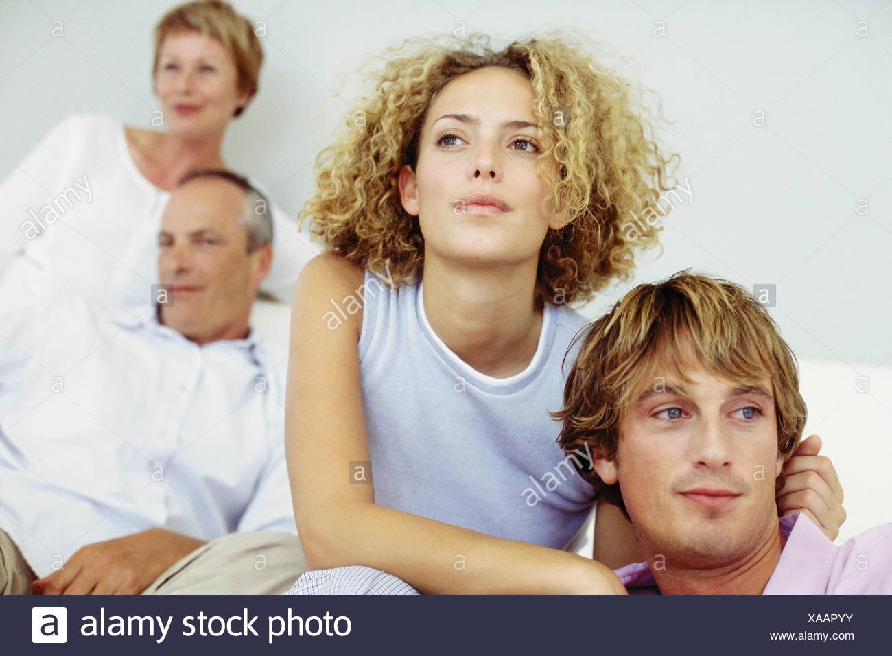 Jeune couple avec leur belle-famille dans l'arrière-plan Photo Stock