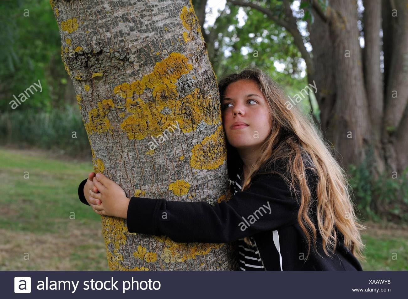 Jeune fille embrassant le tronc d'un frêne, France, Europe. Photo Stock