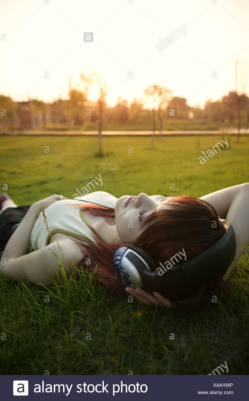 Un jeune Chinois woman lying on lawn listening music Photo Stock