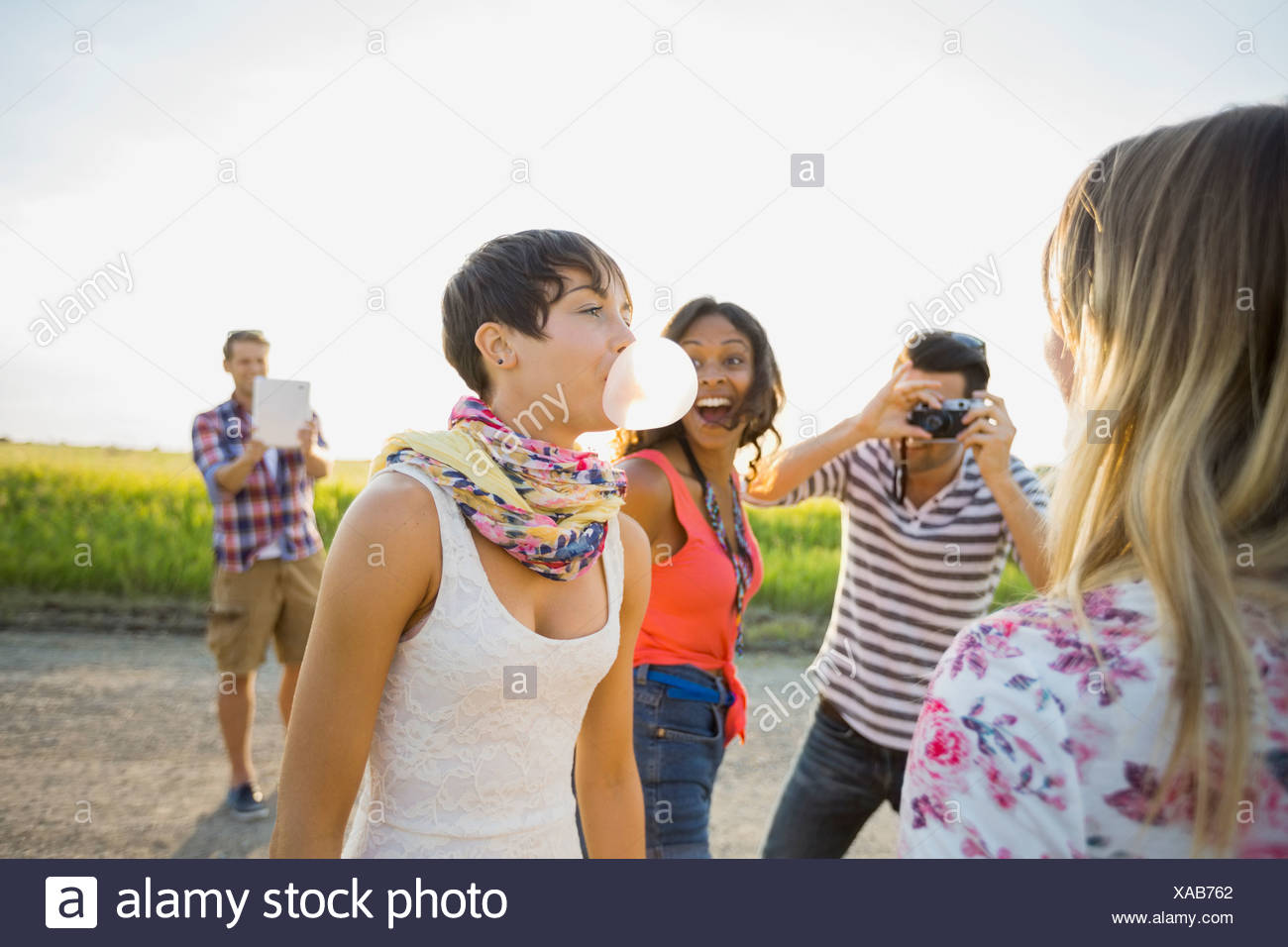 Woman looking at woman blowing bubble gum Photo Stock
