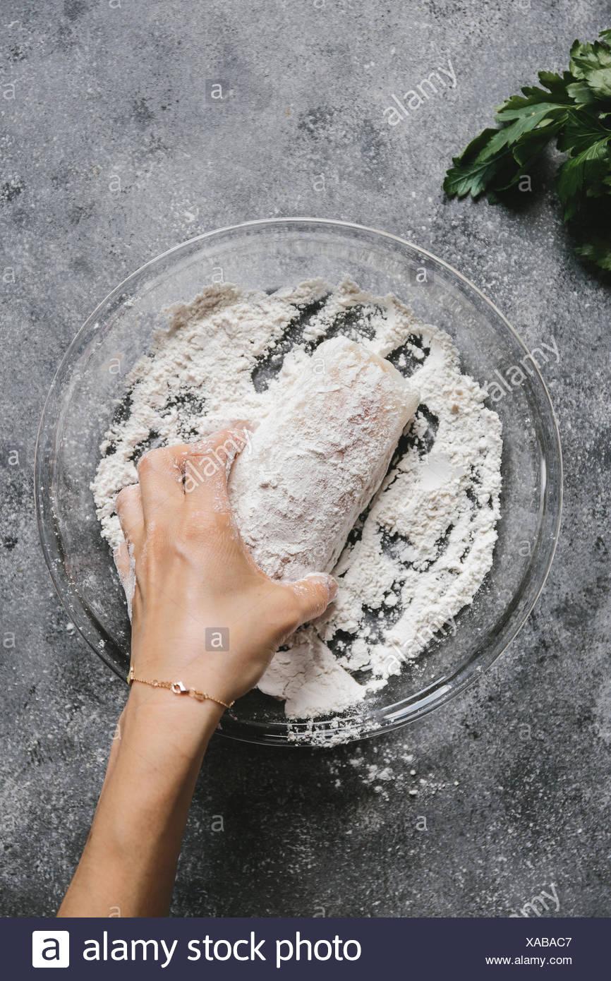 Étape 1/4 Une femme est revêtement d'un filet de poisson avec de la farine. Photo Stock