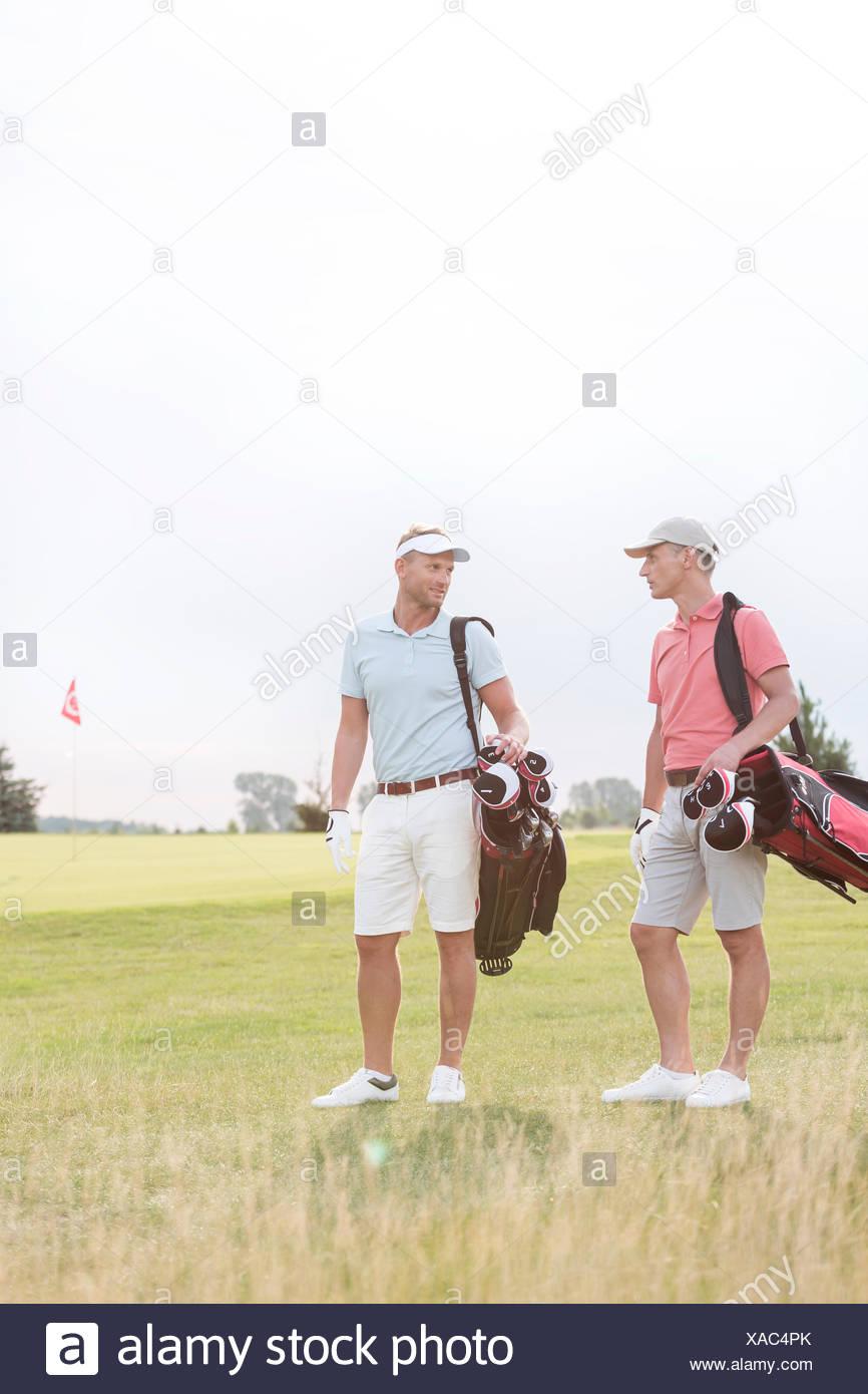 Des hommes de converser au golf contre ciel clair Photo Stock