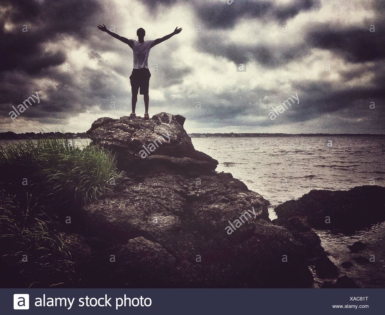 Man With Arms Outstretched Standing On Rocks contre nuages ciel Photo Stock