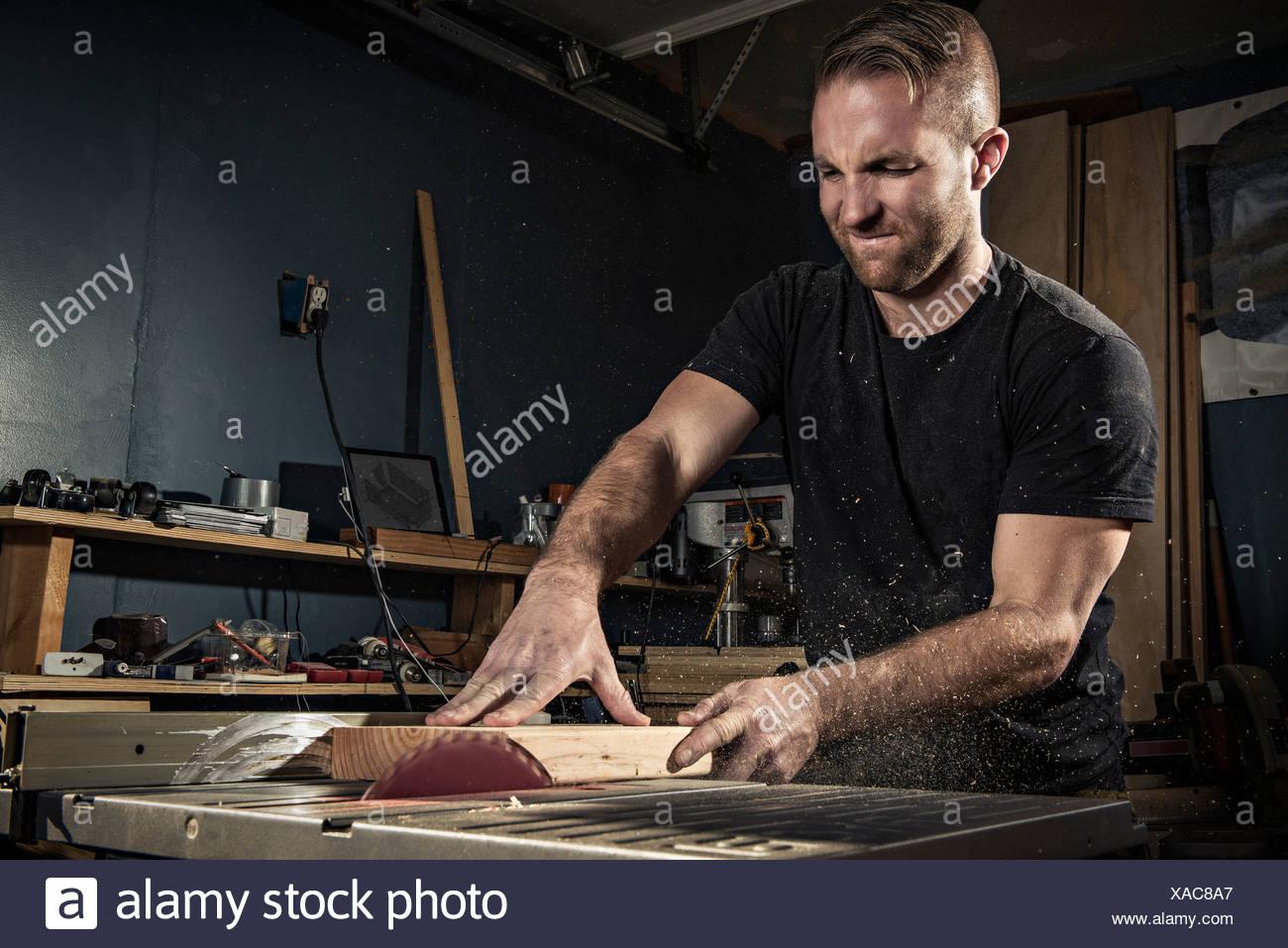 Homme à l'aide d'un menuisier en atelier a vu rotatif Photo Stock