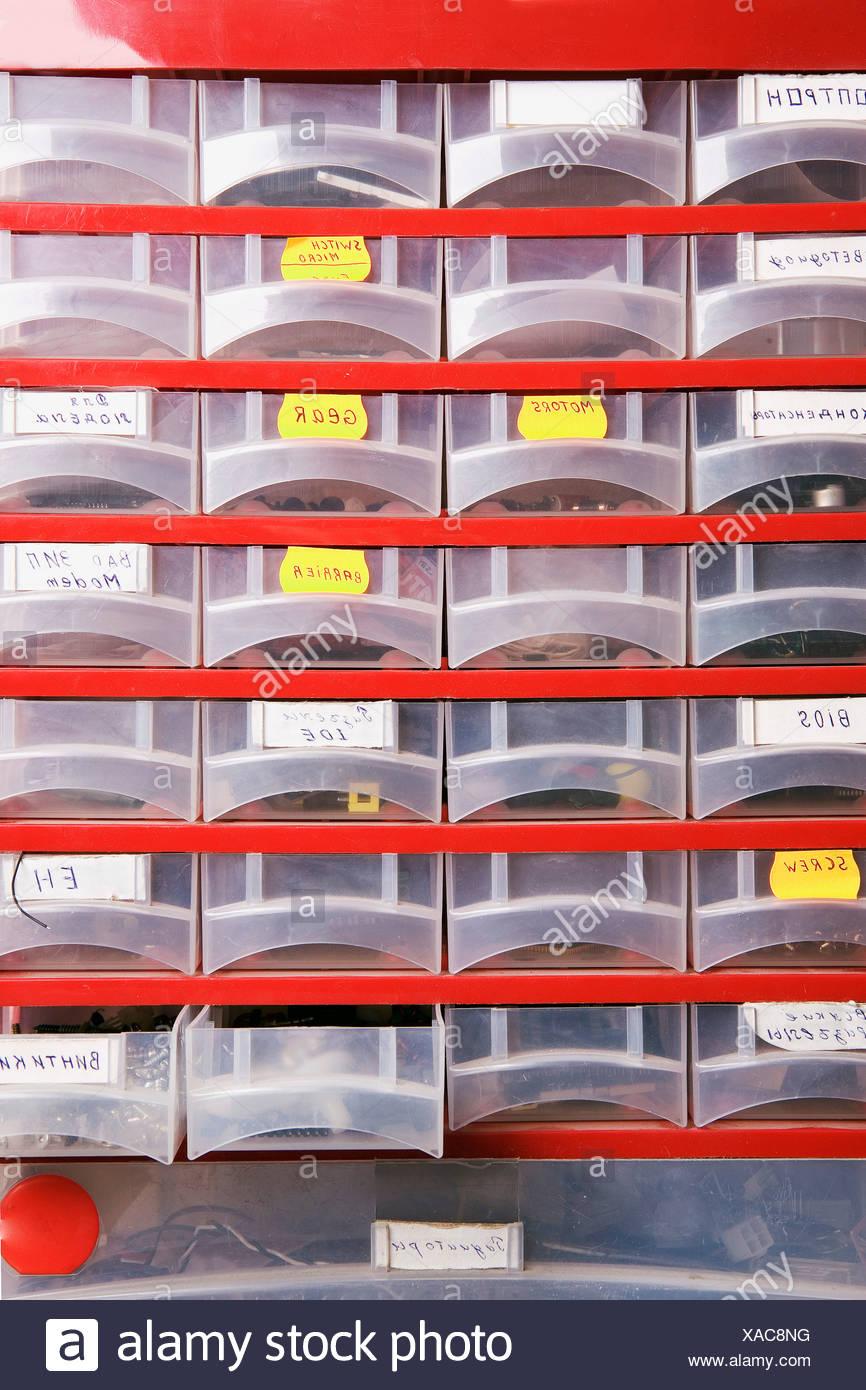 Rangement en plastique avec des pièces détachées à l'atelier informatique Photo Stock