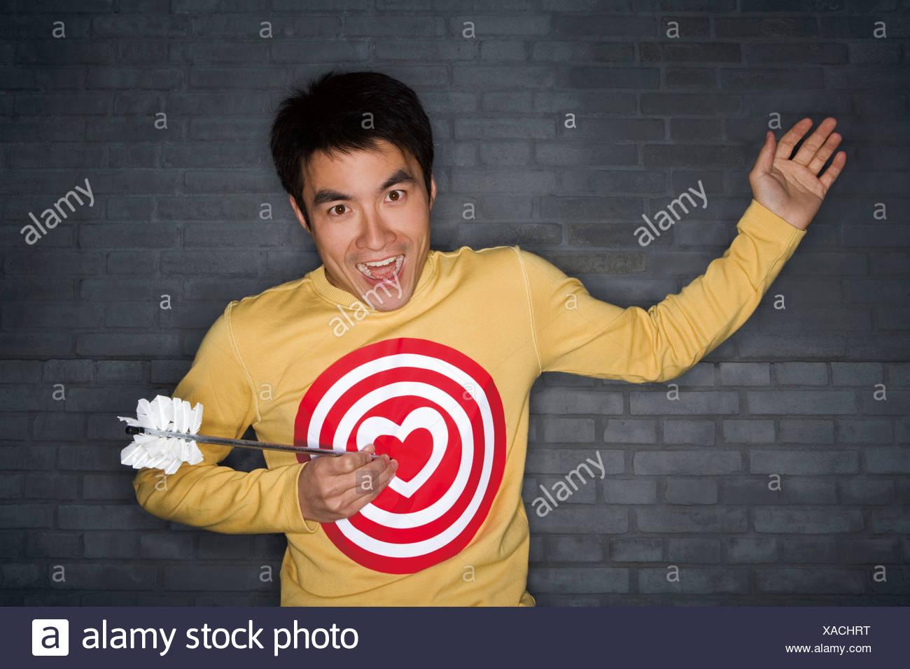 Jeune homme Avec Bulls-Eye Coeur Shirt se faire frapper par 'flèche' de Cupids Photo Stock