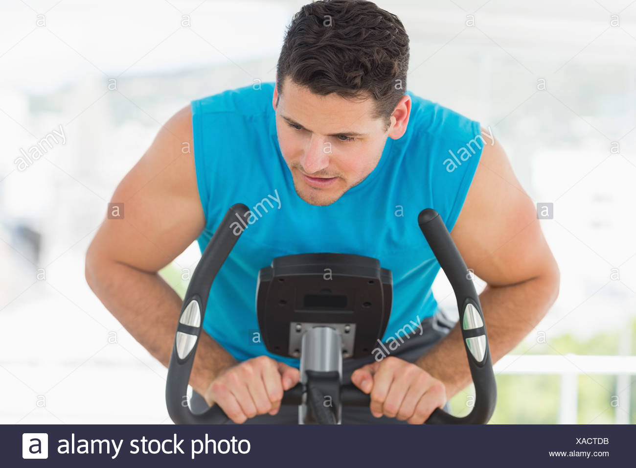 Serious man working out at spinning class Photo Stock