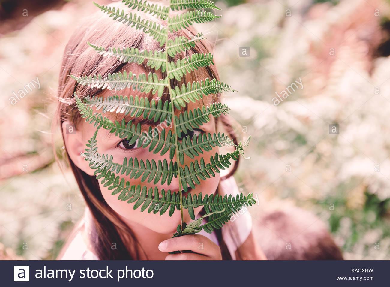 Girl cachant son visage derrière une fronde de fougère Photo Stock