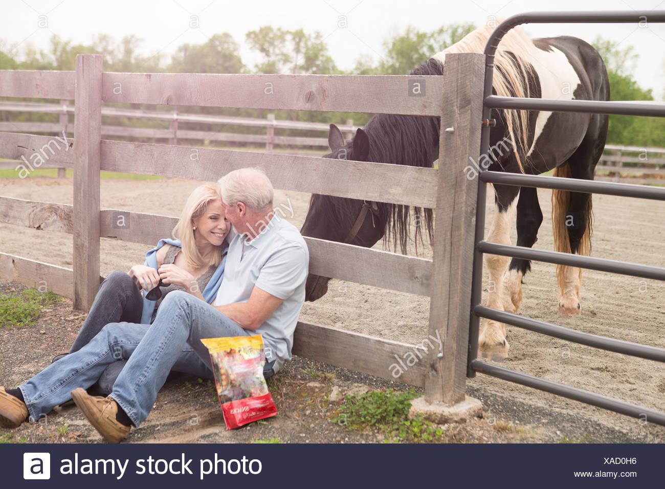 Couple contre clôture et un cheval curieux Photo Stock