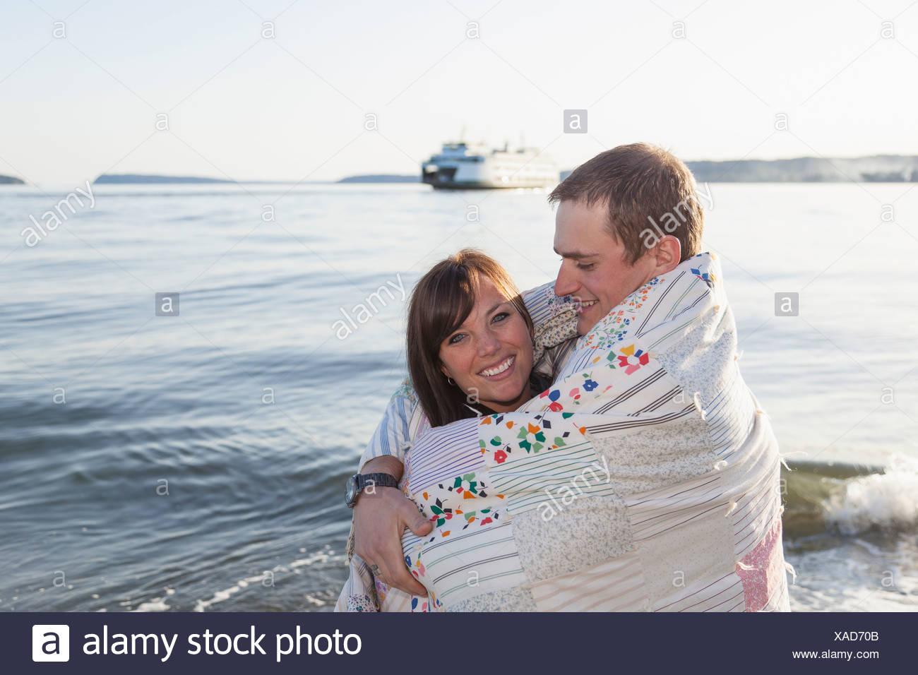 Jeune couple enveloppé dans une couverture à l'autre Photo Stock