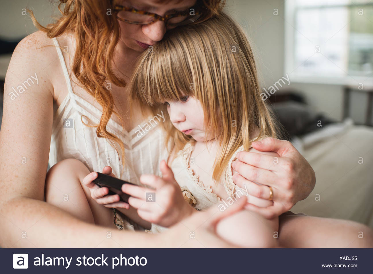 Mother and Daughter, using smartphone Photo Stock