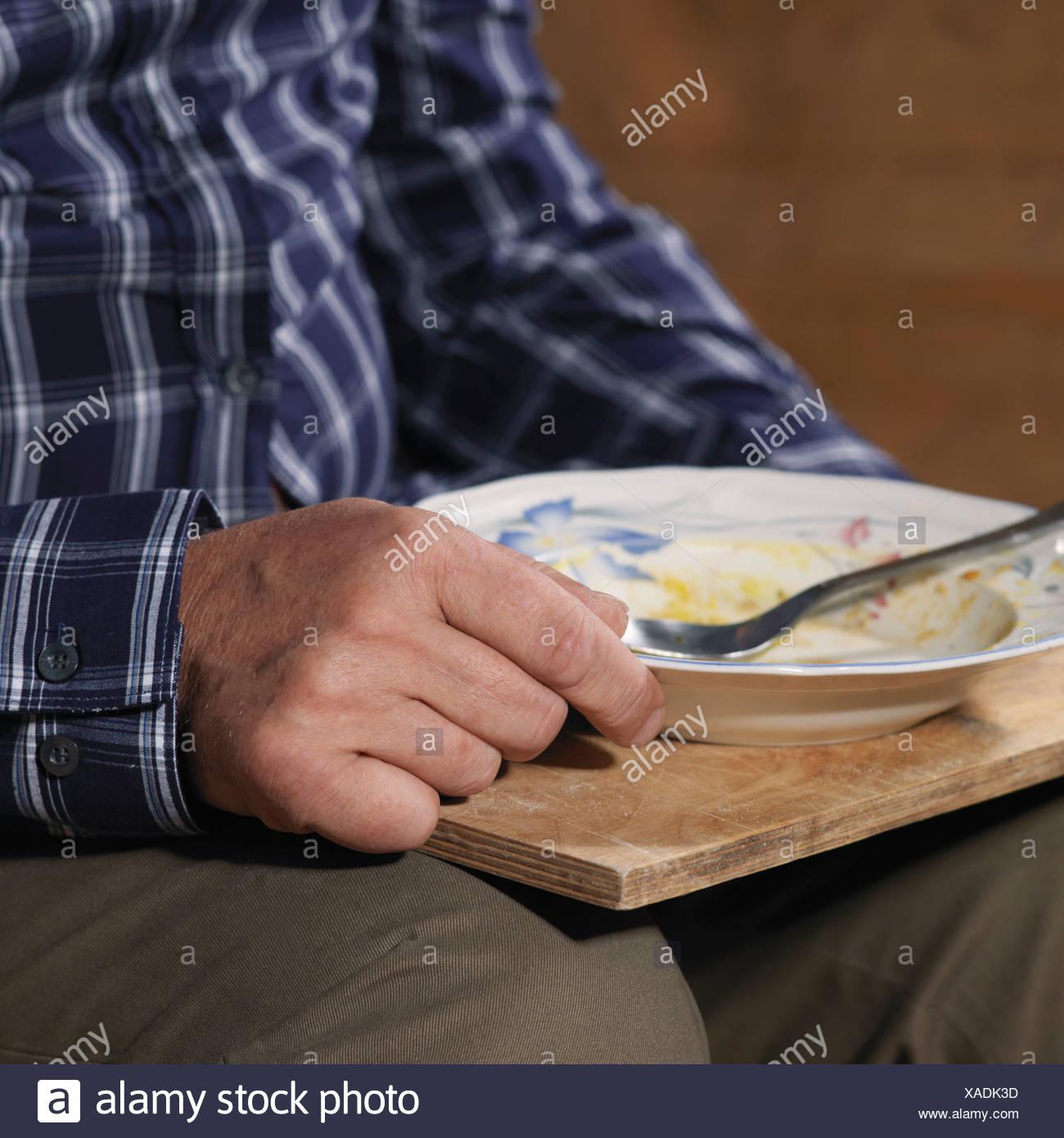 Homme plus âgé de manger sur le bac Banque D'Images