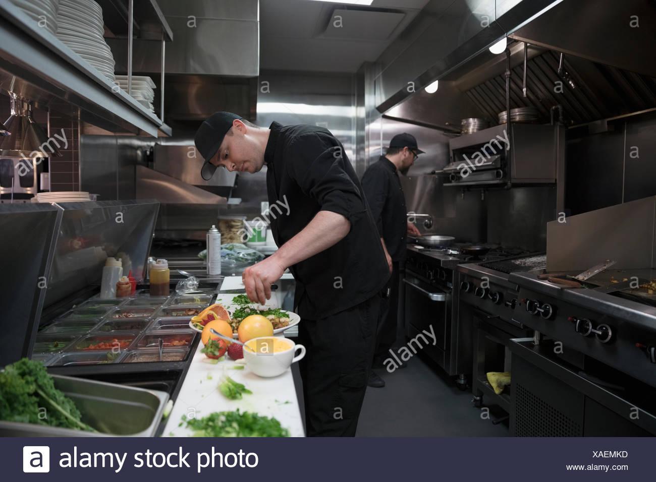 Cuisinier à la chaîne la préparation des aliments dans une cuisine de restaurant Photo Stock