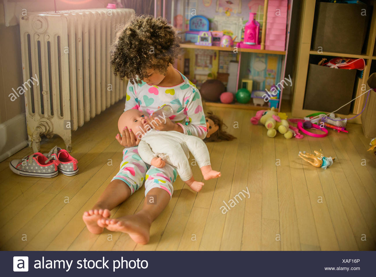 Girl sitting on floor jeux poupée d'alimentation Photo Stock
