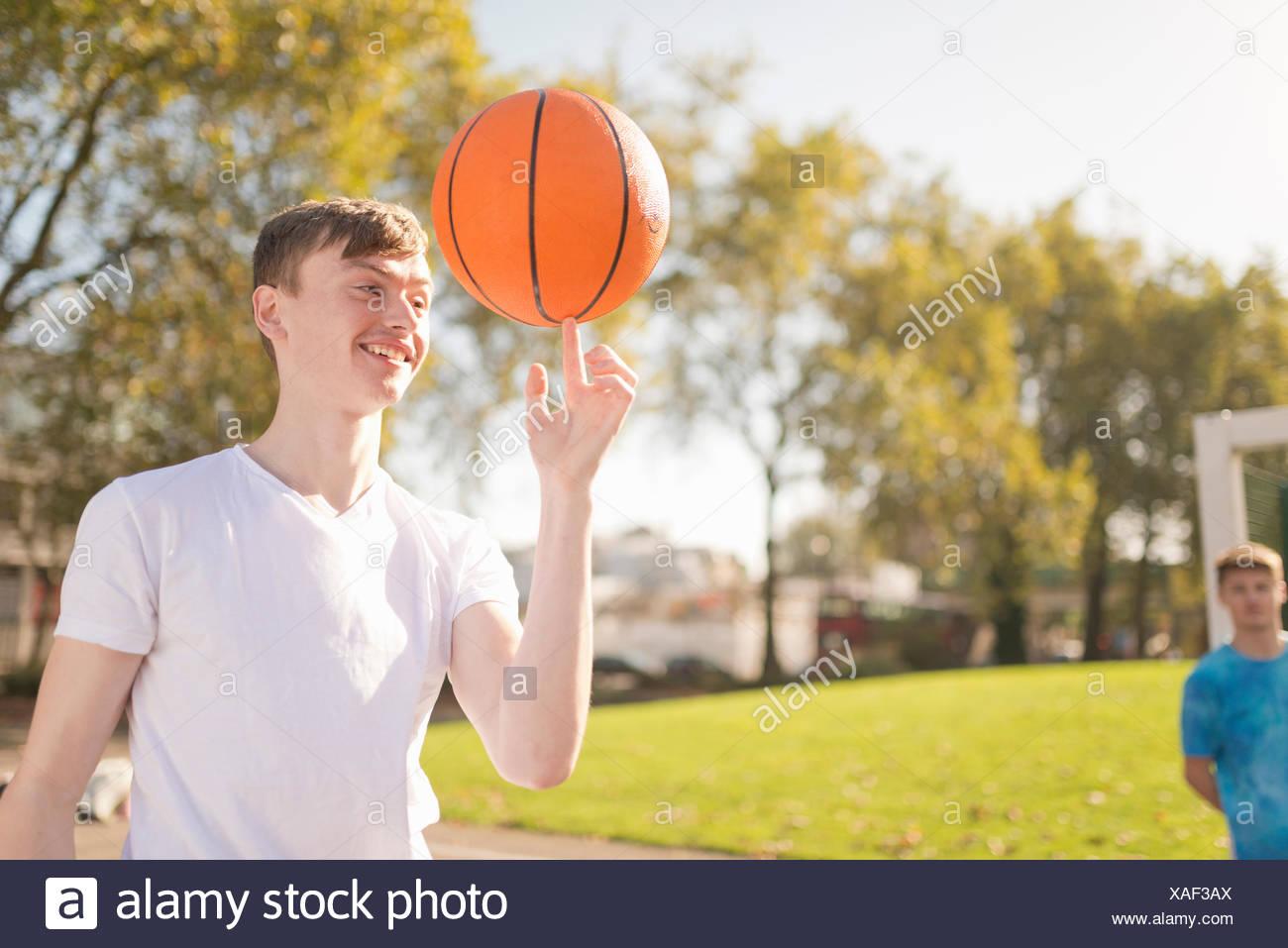 Jeune joueur de basket-ball masculin basket-ball d'équilibrage sur le doigt Photo Stock